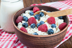 Cottage cheese with berries. Cottage cheese with raspberries and blueberries in brown clay bowl and wooden spoon on red checkered towel Royalty Free Stock Photo