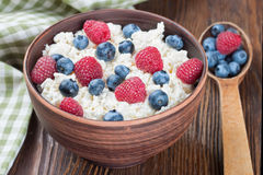 Cottage cheese with berries. Cottage cheese with raspberries and blueberries in brown clay bowl and wooden spoon on wooden background Royalty Free Stock Image