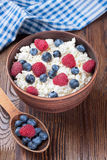 Cottage cheese with berries. Cottage cheese with raspberries and blueberries in brown clay bowl and wooden spoon on wooden background Royalty Free Stock Photo