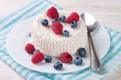 Cottage cheese with berries. Cottage cheese with raspberries and blueberries on white plate Stock Image