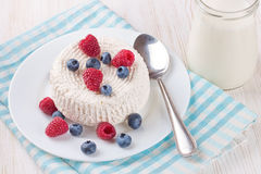 Cottage cheese with berries. Cottage cheese with raspberries and blueberries on white plate Royalty Free Stock Photo