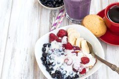 Cottage cheese with berries, smoothies and coffee for breakfast. Cottage cheese with blueberries, raspberries and yogurt, blueberry smoothie and cup of coffee Royalty Free Stock Photos