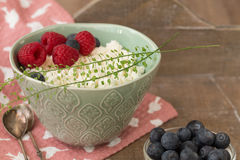 Cottage cheese in blue bowl with raspberries and blueberries on wooden background. Healthy breakfast. Cottage cheese in blue bowl with raspberries on a napkin Stock Image