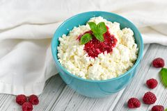 Cottage cheese in blue bowl with raspberries jam and mint on wooden background Royalty Free Stock Images