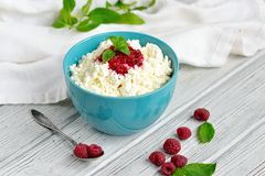 Cottage cheese in blue bowl with raspberries jam and mint on wooden background Royalty Free Stock Image