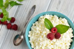 Cottage cheese in blue bowl with raspberries and mint on wooden background Stock Image
