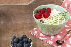 Cottage cheese in bowl with raspberries and blueberries on wooden background. Healthy breakfast .Place under the text. Cottage cheese in blue bowl with Royalty Free Stock Photo