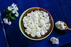 Cottage cheese in a bowl on blue wooden table Royalty Free Stock Images