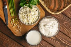 Cottage cheese in bowl, cream and milk and fresh herb on wooden cutting board on table. Healthy food. Cottage cheese in bowl, cream and milk and fresh herb on stock photography