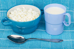 Cottage cheese in bowl, cup of milk and metallic spoon Royalty Free Stock Image