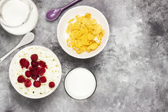 Cottage cheese in bowl with frozen raspberry and cup of cornflakes, milk in glass on a light background. Top view, copy space. Food background Stock Photos