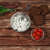 Cottage cheese in bowl of glass, cherry tomatoes, dill and bread Stock Image