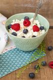 Cottage cheese in bowl with raspberries and blueberries on wooden background. Healthy breakfast .Place under the text. Cottage cheese in blue bowl with Stock Photography