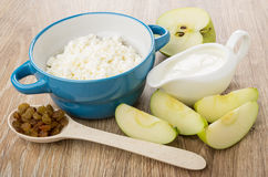 Cottage cheese in bowl, sour cream, pieces of apples, spoon Stock Photos