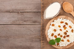 Cottage cheese in bowl with sour cream and raisins on old wooden background with copy space for your text. Top view Royalty Free Stock Images