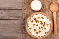 Cottage cheese in bowl with sour cream and raisins on old wooden background with copy space for your text. Top view Royalty Free Stock Photo