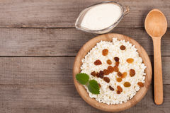 Cottage cheese in bowl with sour cream and raisins on old wooden background with copy space for your text. Top view Royalty Free Stock Photos