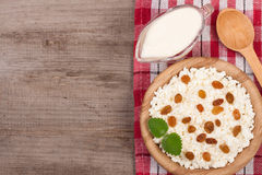 Cottage cheese in bowl with sour cream and raisins on old wooden background with copy space for your text. Top view Stock Images
