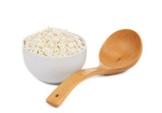 Cottage cheese in bowl with spoon. Royalty Free Stock Image