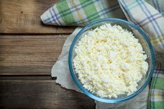 Cottage cheese in bowl. On a wooden background royalty free stock photo