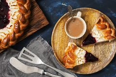 Cottage cheese cake with berry jam and coffee on a dark blue background. Top view, flat lying stock photography
