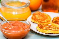 Cottage cheese cakes, honey and quince jam. Close up delicious cottage cheese cakes or syrniki, honey and quince jam on table for breakfast Stock Photos