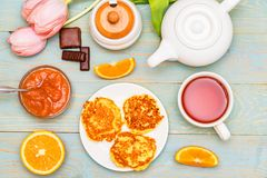 Cottage cheese cakes, honey, quince jam, flower. Top view delicious cottage cheese cakes or syrniki, honey, quince jam, orange, sweets and tulip flower on table Stock Photo