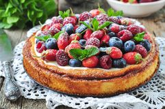 Cottage cheese casserole with fresh strawberries, blueberries, raspberries and mint and powdered sugar Stock Photos
