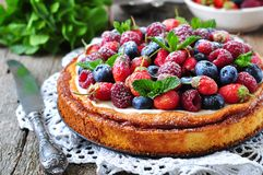 Cottage cheese casserole with fresh strawberries, blueberries, raspberries and mint and powdered sugar. Dinner Royalty Free Stock Photos