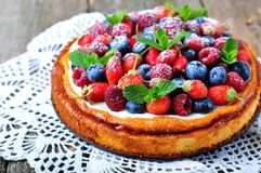 Cottage cheese casserole with fresh strawberries, blueberries, raspberries and mint and powdered sugar. Dinner Stock Images