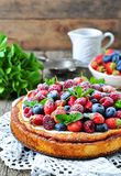Cottage cheese casserole with fresh strawberries, blueberries, raspberries and mint and powdered sugar. Dinner Stock Photo
