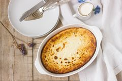 Cottage cheese casserole with raisins, served with cream, a healthy breakfast. Rustic style. Cottage cheese casserole with raisins, served with cream, a healthy Stock Images