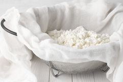 Cottage cheese in cheesecloth. Fresh homemade cottage cheese in cheesecloth and colander on white wooden table Royalty Free Stock Photos
