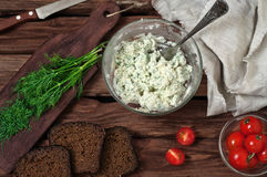 Cottage cheese, cherry tomatoes, dill and bread on wooden backgr Royalty Free Stock Image