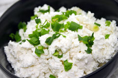 Cottage cheese with chives in black ceramic bowl on rustic woode. N background. Healthy breakfast. Healthy food concept. Soft view Stock Photography