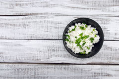 Cottage cheese with chives in black ceramic bowl on rustic woode Stock Image