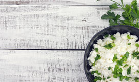 Cottage cheese with chives in black ceramic bowl on rustic woode. N background. Healthy breakfast. Healthy food concept. Top view Royalty Free Stock Images