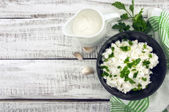 Cottage cheese with chives in black ceramic bowl on rustic woode. N background. Healthy breakfast. Healthy food concept. Top view Royalty Free Stock Photo