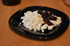 Cottage cheese with confiture on a black plate stock image