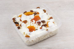 Cottage cheese with dried apricots, raisins and yoghurt in conta Royalty Free Stock Photos
