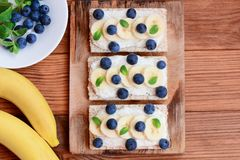 Cottage cheese, fresh bananas and berries sandwiches with crisp bread on wooden board. Vegetarian sandwiches recipe. Top view Stock Photo