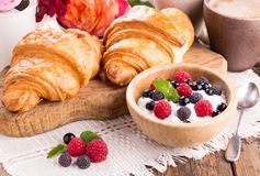 Cottage cheese with fresh berries, cup of coffee and croissants stock photos