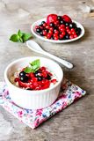 Cottage cheese with fresh berries - strawberry, red and black currant and fresh mint in a small ramekin bowl, selective focus. Org stock photography