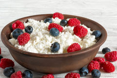 Cottage cheese with fresh raspberries and blueberries in a bowl for healthy breakfast with ripe berries. Close up Royalty Free Stock Photos