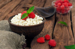 Cottage cheese with fresh raspberries. In a clay bowl on a wooden background, copy space, top view. Dessert Royalty Free Stock Photo