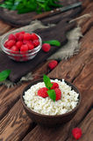 Cottage cheese and fresh raspberries. Cottage cheese with raspberries in a deep bowl on wooden table, copy space. rustic style. close-up Stock Photo