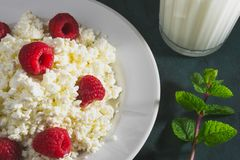 Cottage cheese with raspberry ad milk. Cottage cheese with fresh raspberry, a glass of milk and mint leaves. Plain and healthy rustic breakfast Stock Photo