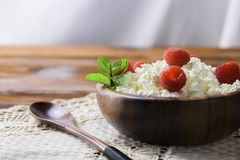 Cottage cheese with fresh raspberry in a wooden bowl on old wooden background with copy space for your text. Top view. Cottage cheese with fresh raspberry in a Stock Photo