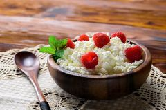 Cottage cheese with fresh raspberry in a wooden bowl on old wood. En background with copy space for your text. Top view Stock Image