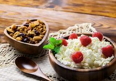 Cottage cheese with fresh raspberry in a wooden bowl on old wood. En background with copy space for your text. Top view Royalty Free Stock Photography